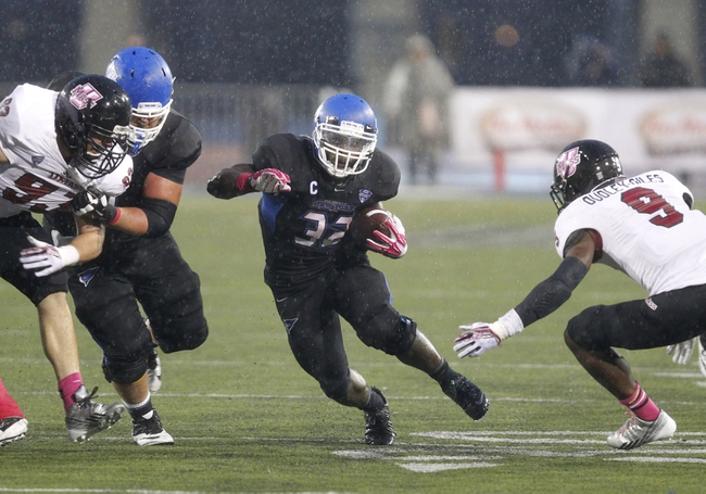 Oct 19, 2013; Buffalo, NY, USA; Buffalo Bulls running back Branden Oliver (32) runs the ball while Massachusetts Minutemen defensive back Trey Dudley-Giles (9) tries to make a tackle during the second half at University of Buffalo Stadium. Buffalo beats Massachusetts 32 to 3.  Mandatory Credit: Timothy T. Ludwig-USA TODAY Sports