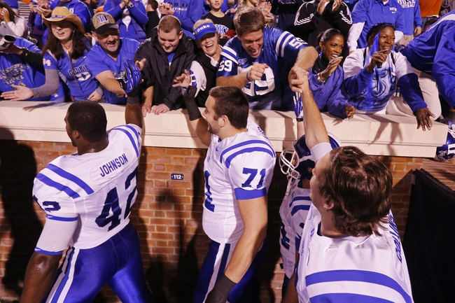 Oct 19, 2013; Charlottesville, VA, USA;  Duke Blue Devils players celebrate with fans in the stands after their game against the Virginia Cavaliers at Scott Stadium. The Blue Devils won 35-22. Mandatory Credit: Geoff Burke-USA TODAY Sports