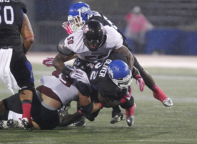 Oct 19, 2013; Buffalo, NY, USA; Massachusetts Minutemen defensive lineman Justin Anderson (50) tackles Buffalo Bulls running back Branden Oliver (32) during the second half at University of Buffalo Stadium. Buffalo beats Massachusetts 32 to 3.  Mandatory Credit: Timothy T. Ludwig-USA TODAY Sports