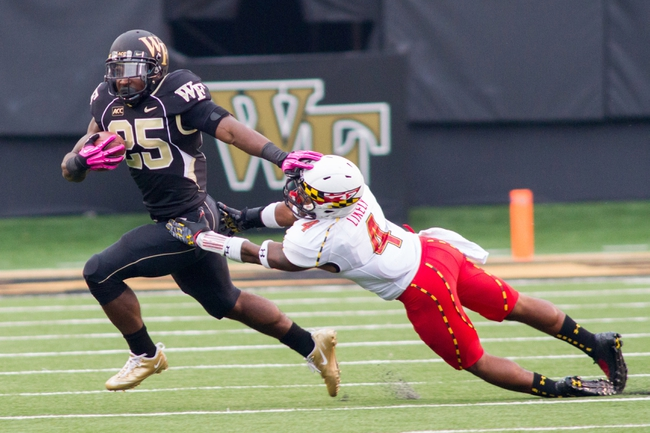 Oct 19, 2013; Winston-Salem, NC, USA; Wake Forest Demon Deacons running back Josh D. Harris (25) stiff arms Maryland Terrapins defensive back William Likely (4) during the third quarter at BB&T Field. Wake defeated Maryland 34-10. Mandatory Credit: Jeremy Brevard-USA TODAY Sports