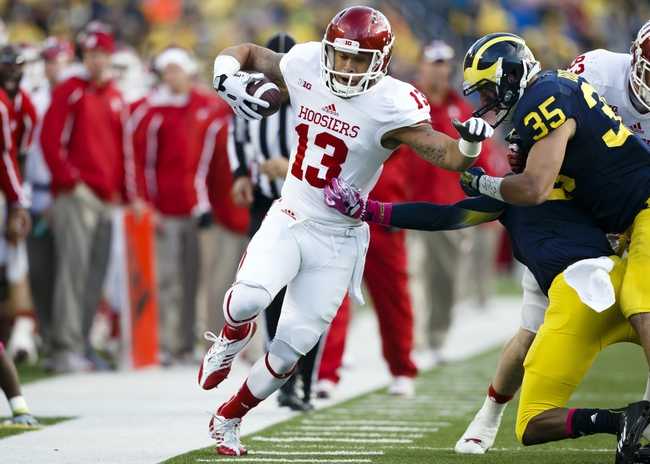 Oct 19, 2013; Ann Arbor, MI, USA; Indiana Hoosiers wide receiver Kofi Hughes (13) runs the ball down the sidelines as Michigan Wolverines linebacker Joe Bolden (35) forces him out in the second half at Michigan Stadium. Michigan won 63-47. Mandatory Credit: Rick Osentoski-USA TODAY Sports
