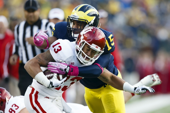 Oct 19, 2013; Ann Arbor, MI, USA; Indiana Hoosiers wide receiver Kofi Hughes (13) is tackled by Michigan Wolverines linebacker James Ross III (15) in the second half at Michigan Stadium. Michigan won 63-47. Mandatory Credit: Rick Osentoski-USA TODAY Sports