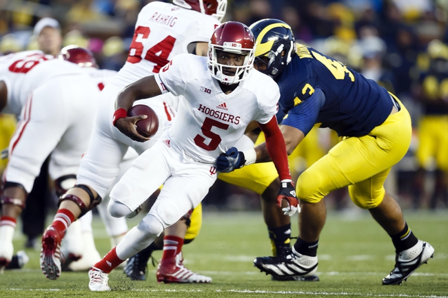 Oct 19, 2013; Ann Arbor, MI, USA; Indiana Hoosiers quarterback Tre Roberson (5) runs the ball past Michigan Wolverines defensive lineman Chris Wormley (43) in the second half at Michigan Stadium. Michigan won 63-47. Mandatory Credit: Rick Osentoski-USA TODAY Sports
