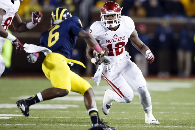 Oct 19, 2013; Ann Arbor, MI, USA; Indiana Hoosiers running back Stephen Houston (12) runs the ball at Michigan Wolverines defensive back Raymon Taylor (6) in the second half at Michigan Stadium. Michigan won 63-47. Mandatory Credit: Rick Osentoski-USA TODAY Sports