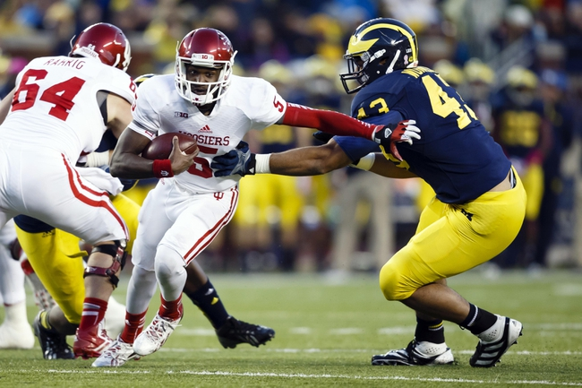 Oct 19, 2013; Ann Arbor, MI, USA; Indiana Hoosiers quarterback Tre Roberson (5) avoids a tackle by Michigan Wolverines defensive lineman Chris Wormley (43) in the second half at Michigan Stadium. Michigan won 63-47. Mandatory Credit: Rick Osentoski-USA TODAY Sports
