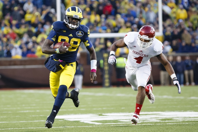 Oct 19, 2013; Ann Arbor, MI, USA; Michigan Wolverines quarterback Devin Gardner (98) runs the ball by Indiana Hoosiers linebacker Forisse Hardin (4) in the second half at Michigan Stadium. Michigan won 63-47. Mandatory Credit: Rick Osentoski-USA TODAY Sports