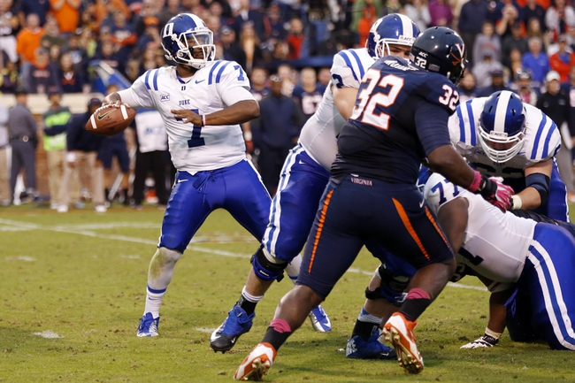 Oct 19, 2013; Charlottesville, VA, USA;  Duke Blue Devils quarterback Anthony Boone (7) throws the ball as Virginia Cavaliers defensive end Mike Moore (32) chases in the fourth quarter at Scott Stadium. The Blue Devils won 35-22. Mandatory Credit: Geoff Burke-USA TODAY Sports
