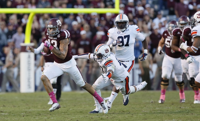 Oct 19, 2013; College Station, TX, USA; Texas A&M Aggies wide receiver Mike Evans (13) attempts to elude Auburn Tigers linebacker Kris Frost (right) during the second half at Kyle Field. Tigers won 45-41. Mandatory Credit: Soobum Im-USA TODAY Sports