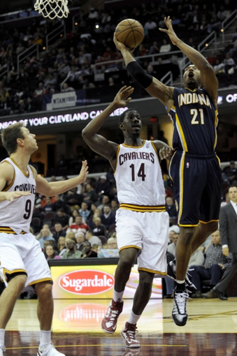 Oct 19, 2013; Cleveland, OH, USA; Indiana Pacers forward David West (21) drives on Cleveland Cavaliers center Henry Sims (14) during the third quarter at Quicken Loans Arena. The Pacers beat the Cavaliers 102-79. Mandatory Credit: Ken Blaze-USA TODAY Sports