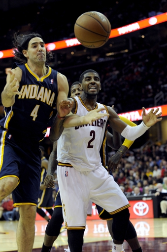 Oct 19, 2013; Cleveland, OH, USA; Indiana Pacers forward Luis Scola (4) and Cleveland Cavaliers guard Kyrie Irving (2) go for a loose ball during the third quarter at Quicken Loans Arena. The Pacers beat the Cavaliers 102-79. Mandatory Credit: Ken Blaze-USA TODAY Sports