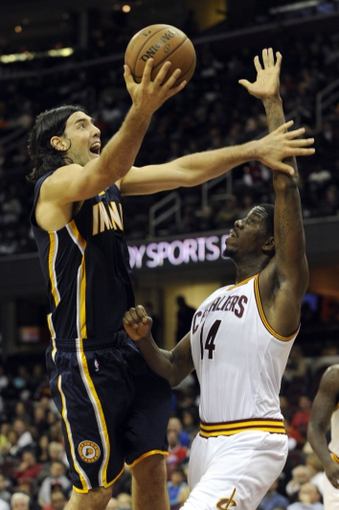 Oct 19, 2013; Cleveland, OH, USA; Indiana Pacers forward Luis Scola (4) shoots over Cleveland Cavaliers center Henry Sims (14) during the fourth quarter at Quicken Loans Arena. The Pacers beat the Cavaliers 102-79. Mandatory Credit: Ken Blaze-USA TODAY Sports
