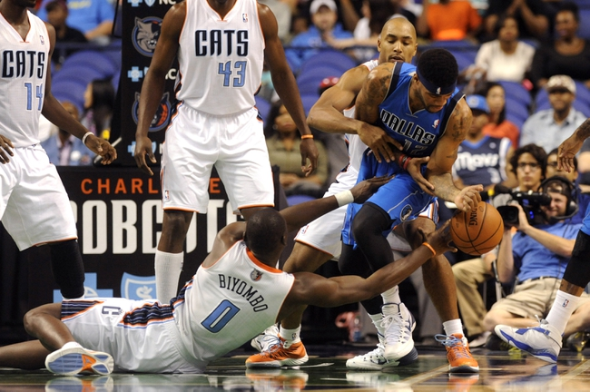 Oct 19, 2013; Greensboro, NC, USA; Dallas Mavericks guard forward D.J. Kennedy (12) and Charlotte Bobcats forward center Bismack Biyombo (0) battle for the ball  during the game at Greensboro Coliseum. The Mavericks won 89-83. Mandatory Credit: Sam Sharpe-USA TODAY Sports