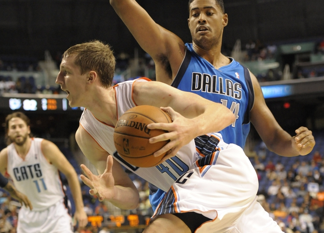 Oct 19, 2013; Greensboro, NC, USA; Charlotte Bobcats forward Cody Zeller (40) dribbles the ball past Dallas Mavericks center Fab Melo (14) during the game at Greensboro Coliseum. The Mavericks won 89-83. Mandatory Credit: Sam Sharpe-USA TODAY Sports
