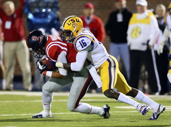 Oct 19, 2013; Oxford, MS, USA; Mississippi Rebels wide receiver Donte Moncrief (12) catches a pass and is tackled by LSU Tigers defensive back Tre'Davious White (16) during the game at Vaught-Hemingway Stadium. Mississippi Rebels defeat the LSU Tigers 27-24.  Mandatory Credit: Spruce Derden-USA TODAY Sports
