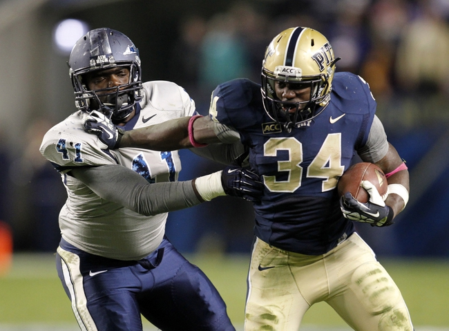 Oct 19, 2013; Pittsburgh, PA, USA; Pittsburgh Panthers running back Isaac Bennett (34) rushes the ball past Old Dominion Monarchs linebacker Richie Staton (41) during the fourth quarter at Heinz Field.  Pittsburgh won 35-24. Mandatory Credit: Charles LeClaire-USA TODAY Sports