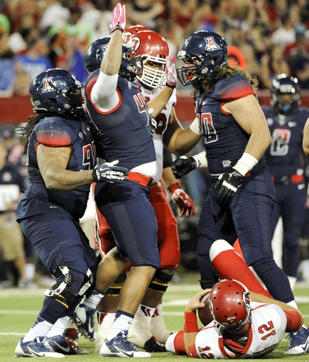 Oct 19, 2013; Tucson, AZ, USA; Arizona Wildcats defensive lineman Justin Washington (43) is congratulated by  defensive lineman Tevin Hood (98) and defensive lineman Dan Pettinato (90) after sacking Utah Utes quarterback Adam Schulz (12) during the third quarter at Arizona Stadium. Arizona beat Utah 35-44. Mandatory Credit: Casey Sapio-USA TODAY Sports