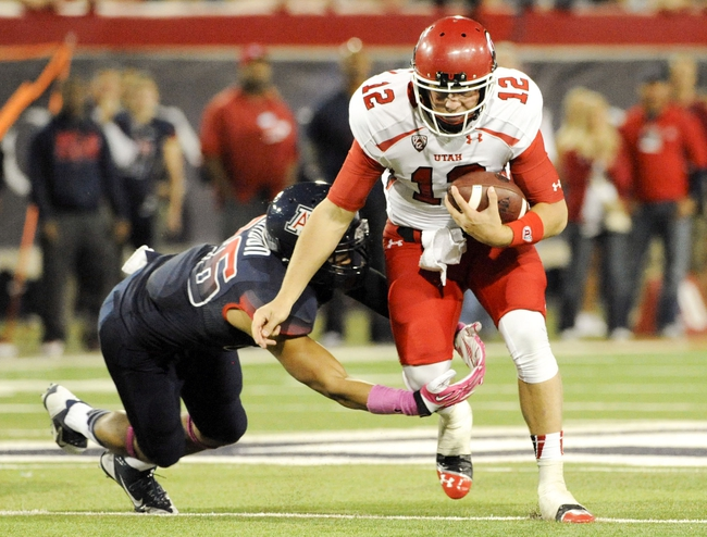 Oct 19, 2013; Tucson, AZ, USA; Utah Utes quarterback Adam Schulz (12) is tackled by Arizona Wildcats free safety Jourdon Grandon (26) during the fourth quarter at Arizona Stadium. Arizona beat Utah 35-44. Mandatory Credit: Casey Sapio-USA TODAY Sports