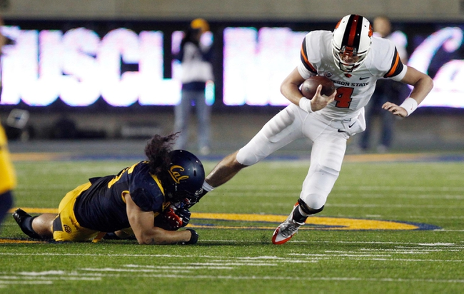 Oct 19, 2013; Berkeley, CA, USA; California Golden Bears defensive end Puka Lopa (75) holds onto the ankle of Oregon State Beavers quarterback Sean Mannion (4) for a sack during the third quarter at Memorial Stadium. The Oregon State Beavers defeated the California Golden Bears 49-17. Mandatory Credit: Kelley L Cox-USA TODAY Sports