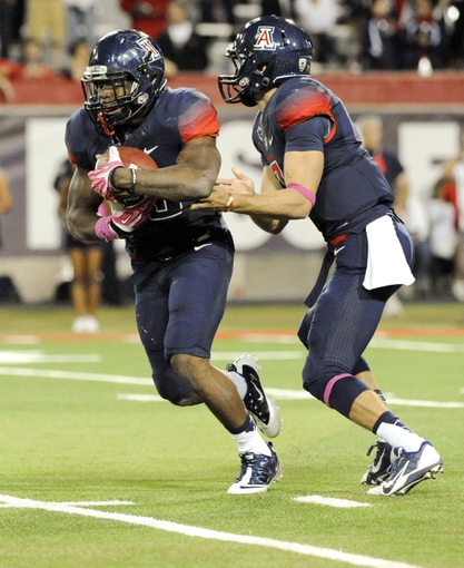 Oct 19, 2013; Tucson, AZ, USA; Arizona Wildcats running back KaDeem Carey (25) runs the ball after the hand off from quarterback B.J. Denker (7) during the third quarter against the Utah Utes at Arizona Stadium. Arizona beat Utah 35-44. Mandatory Credit: Casey Sapio-USA TODAY Sports