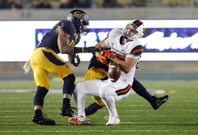 Oct 19, 2013; Berkeley, CA, USA; California Golden Bears linebacker Khairi Fortt (11) and defensive back Damariay Drew (27) defend the pass intended for Oregon State Beavers tight end Caleb Smith (10) during the fourth quarter at Memorial Stadium. The Oregon State Beavers defeated the California Golden Bears 49-17. Mandatory Credit: Kelley L Cox-USA TODAY Sports