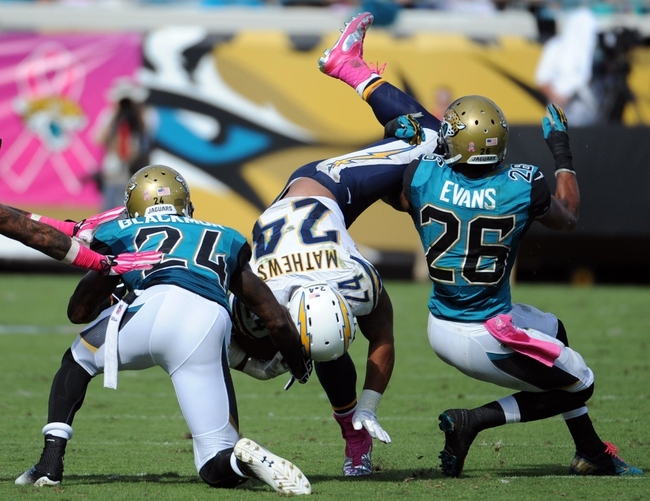 Oct 20, 2013; Jacksonville, FL, USA; San Diego Chargers running back Ryan Mathews (24) runs the ball past Jacksonville Jaguars cornerback Will Blackmon (24) and safety Josh Evans (26) during the second half at EverBank Field. Mandatory Credit: Melina Vastola-USA TODAY Sports
