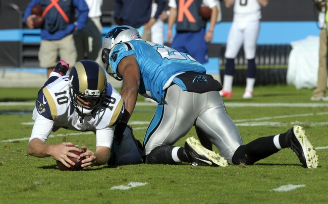 Oct 20, 2013; Charlotte, NC, USA; St. Louis Rams quarterback Kellen Clemens fumbles the ball after being hit by Carolina safety Mike Mitchell (21) during the game at Bank of America Stadium. Panthers win 30-15. Mandatory Credit: Sam Sharpe-USA TODAY Sports