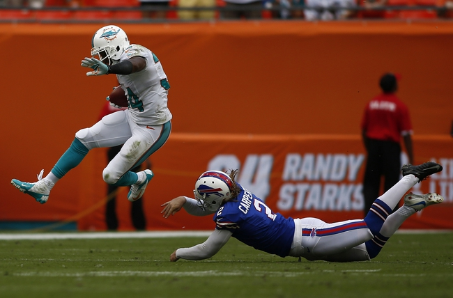 Oct 20, 2013; Miami Gardens, FL, USA; Miami Dolphins running back Marcus Thigpen (34) leaps over Buffalo Bills punter Dan Carpenter in the fourth quarter at Sun Life Stadium. The Bills won 23-21. Mandatory Credit: Robert Mayer-USA TODAY Sports
