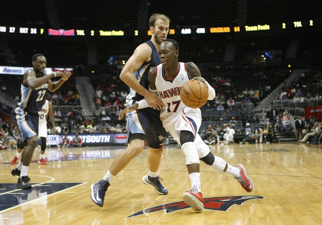 Oct 10, 2013; Atlanta, GA, USA; Atlanta Hawks point guard Dennis Schroder (17) drives past Memphis Grizzlies shooting guard Nick Calathes (12) in the fourth quarter at Philips Arena. The Grizzlies defeated the Hawks 90-82. Mandatory Credit: Brett Davis-USA TODAY Sports