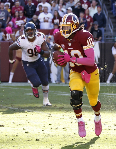 Oct 20, 2013; Landover, MD, USA; Washington Redskins quarterback Robert Griffin III (10) runs with the ball as Chicago Bears defensive end Corey Wootton (98) chases in the third quarter at FedEx Field. The Redskins won 45-41. Mandatory Credit: Geoff Burke-USA TODAY Sports