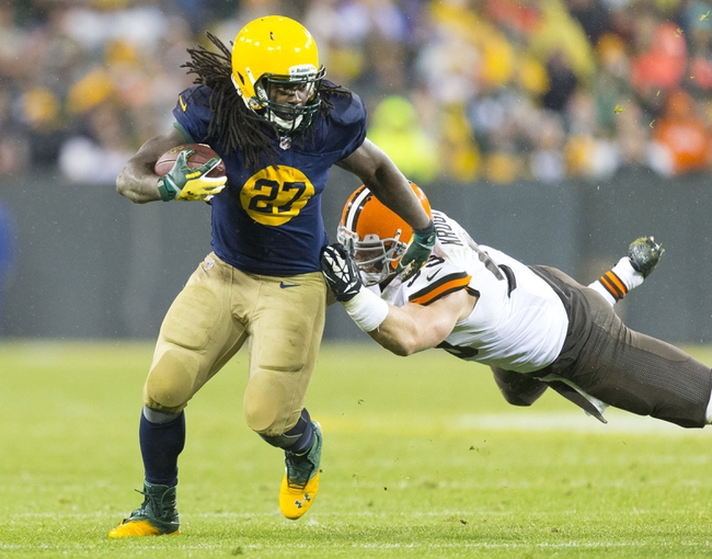 Oct 20, 2013; Green Bay, WI, USA; Green Bay Packers running back Eddie Lacy (27) rushes with the football as Cleveland Browns linebacker Paul Kruger (99) dives from behind during the fourth quarter at Lambeau Field.  Green Bay won 31-13.  Mandatory Credit: Jeff Hanisch-USA TODAY Sports