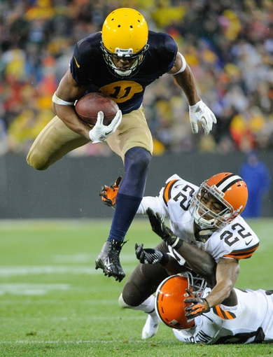 Oct 20, 2013; Green Bay, WI, USA;  Green Bay Packers wide receiver Jarrett Boykin leaps over Cleveland Browns defensive back Buster Skrine (22) and defensive back Tashaun Gipson (39) for a first down in the 4th quarter at Lambeau Field. Mandatory Credit: Benny Sieu-USA TODAY Sports
