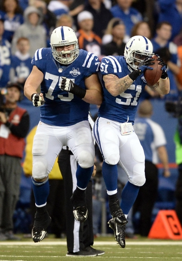 Oct 20, 2013; Indianapolis, IN, USA; Indianapolis Colts inside linebacker Pat Angerer (51) celebrates with guard Mike McGlynn (75) after an interception against the Denver Broncos in the second half during the game at Lucas Oil Stadium. Mandatory Credit: Ron Chenoy-USA TODAY Sports