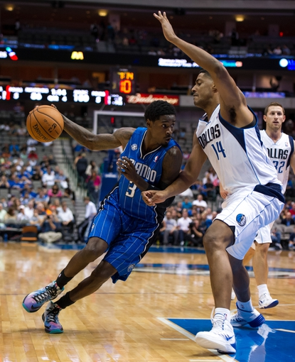 Oct 14, 2013; Dallas, TX, USA; Dallas Mavericks center Fab Melo (14) guards Orlando Magic point guard Manny Harris (3) during the game at the American Airlines Center. The Magic defeated the Mavericks 102-94. Mandatory Credit: Jerome Miron-USA TODAY Sports