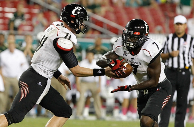 Oct 5, 2013; Tampa, FL, USA; Cincinnati Bearcats quarterback Brendon Kay (11) hands the ball off to running back Tion Green (7) against the South Florida Bulls during the second half at Raymond James Stadium. South Florida Bulls defeated the Cincinnati Bearcats 26-20. Mandatory Credit: Kim Klement-USA TODAY Sports