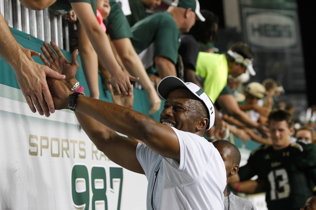Oct 5, 2013; Tampa, FL, USA; South Florida Bulls head coach Willie Taggart high-fives fans after they beat the Cincinnati Bearcats during the second half at Raymond James Stadium. South Florida Bulls defeated the Cincinnati Bearcats 26-20. Mandatory Credit: Kim Klement-USA TODAY Sports