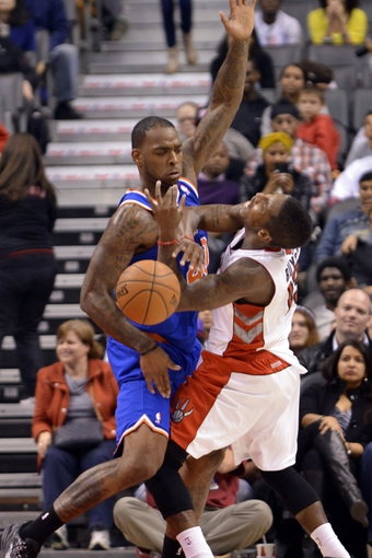 Oct 21, 2013; Toronto, Ontario, CAN; Toronto Raptors point guard Dwight Buycks (13) is fouled by New York Knicks power forward Josh Powell (20) in the second half of a game at the Air Canada Centre.Toronto won the game in triple overtime123-120. Mandatory Credit: Mark Konezny-USA TODAY Sports