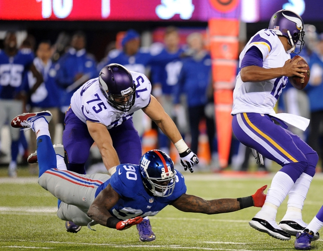 Oct 21, 2013; East Rutherford, NJ, USA; Minnesota Vikings quarterback Josh Freeman (12) eludes New York Giants defensive end Jason Pierre-Paul (90) during the second half at MetLife Stadium. The Giants won the game 23-7. Mandatory Credit: Joe Camporeale-USA TODAY Sports