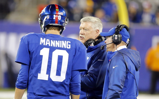 Oct 21, 2013; East Rutherford, NJ, USA;  New York Giants offensive coordinator Kevin Gilbride (center) talks to quarterback Eli Manning (10) as Tom Coughlin listens during the second half against the Minnesota Vikings at MetLife Stadium. New York Giants defeat the Minnesota Vikings 23-7. Mandatory Credit: Jim O'Connor-USA TODAY Sports