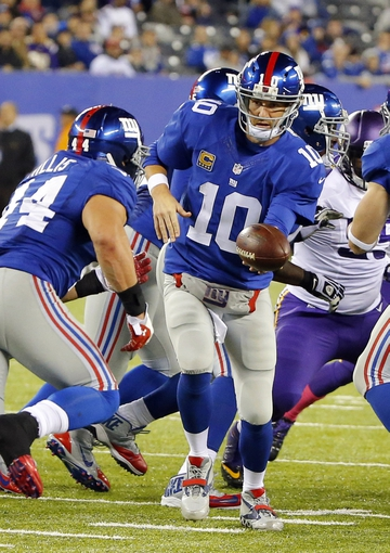 Oct 21, 2013; East Rutherford, NJ, USA;  New York Giants quarterback Eli Manning (10) hands off to running back Peyton Hillis (44) during the second half against the Minnesota Vikings at MetLife Stadium. New York Giants defeat the Minnesota Vikings 23-7. Mandatory Credit: Jim O'Connor-USA TODAY Sports