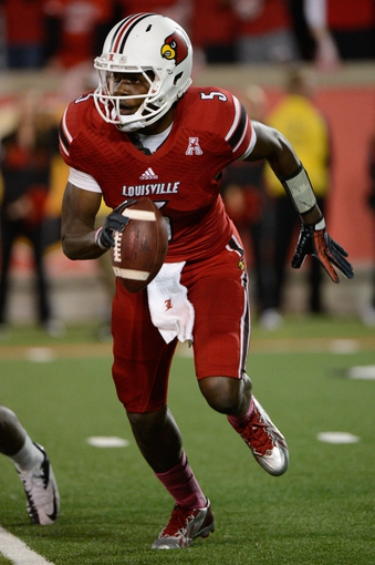 Oct 18, 2013; Louisville, KY, USA; Louisville Cardinals quarterback Teddy Bridgewater (5) scrambles with the ball during the second half of play against the UCF Knights at Papa John's Cardinal Stadium. Central Florida defeated Louisville 38-35.  Mandatory Credit: Jamie Rhodes-USA TODAY Sports