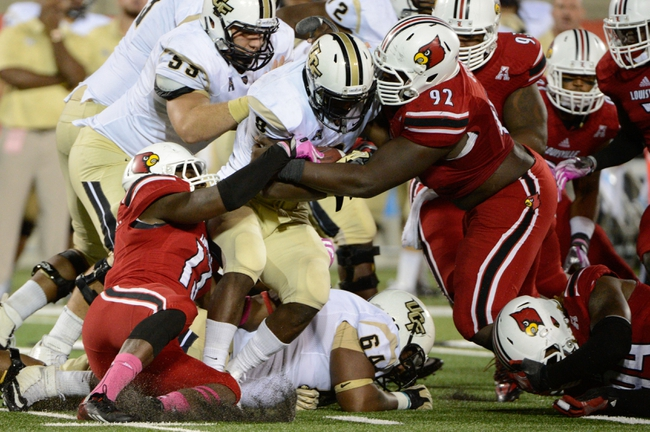 Oct 18, 2013; Louisville, KY, USA; Louisville Cardinals defensive tackle Brandon Dunn (92) and linebacker James Burgess (13) tackle UCF Knights running back Storm Johnson (8) during the second half of play at Papa John's Cardinal Stadium. Central Florida defeated Louisville 38-35.  Mandatory Credit: Jamie Rhodes-USA TODAY Sports