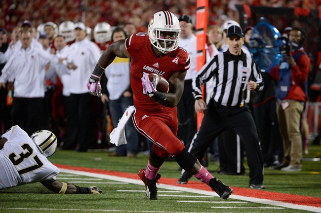 Oct 18, 2013; Louisville, KY, USA; Louisville Cardinals running back Dominique Brown (10) runs the ball in for a touchdown against the UCF Knights during the second half of play at Papa John's Cardinal Stadium. Central Florida defeated Louisville 38-35.  Mandatory Credit: Jamie Rhodes-USA TODAY Sports