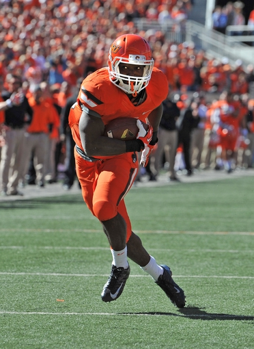Oct 19, 2013; Stillwater, OK, USA; Oklahoma State Cowboys running back Rennie Childs (23) rushes for a touchdown against the Texas Christian Horned Frogs during the second half at Boone Pickens Stadium. Mandatory Credit: Peter G. Aiken-USA TODAY Sports