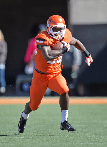 Oct 19, 2013; Stillwater, OK, USA; Oklahoma State Cowboys running back Rennie Childs (23) rushes up field against the Texas Christian Horned Frogs during the second half at Boone Pickens Stadium. Mandatory Credit: Peter G. Aiken-USA TODAY Sports