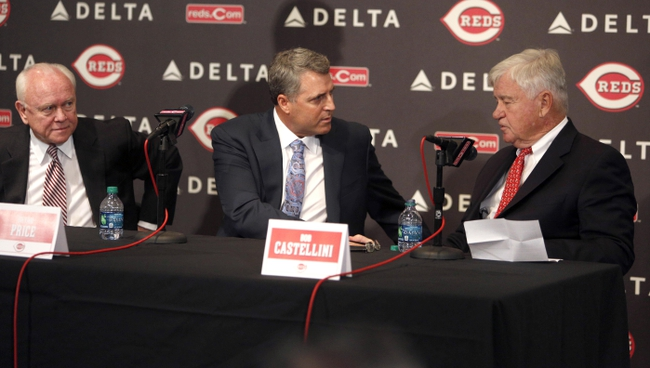 Oct 22, 2013; Cincinnati, OH, USA; Cincinnati Reds new manager Bryan Price (middle) shakes hands with team president Bob Castellini (right) along with general manger Walt Jocketty (left) during a news conference at Great American Ballpark. Mandatory Credit: David Kohl-USA TODAY Sports
