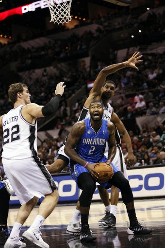 Oct 22, 2013; San Antonio, TX, USA; Orlando Magic forward Kyle O'Quinn (2) looks to shoot against San Antonio Spurs forward Tiago Splitter (22) and Tim Duncan (behind) during the first half at AT&T Center. Mandatory Credit: Soobum Im-USA TODAY Sports