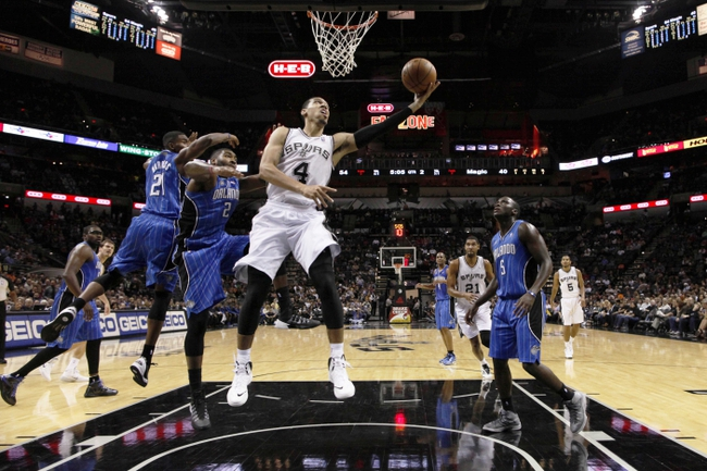 Oct 22, 2013; San Antonio, TX, USA; San Antonio Spurs guard Danny Green (4) drives to the basket past Orlando Magic forward Kyle O'Quinn (2) during the first half at AT&T Center. Mandatory Credit: Soobum Im-USA TODAY Sports
