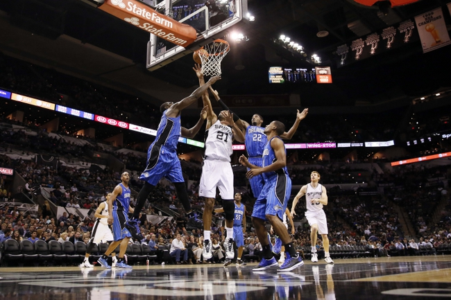 Oct 22, 2013; San Antonio, TX, USA; San Antonio Spurs forward Tim Duncan (21) shoots while Orlando Magic forward Jason Maxiell (left) and  Solomon Jones (right) defend during the second half at AT&T Center. The Spurs won 123-101. Mandatory Credit: Soobum Im-USA TODAY Sports