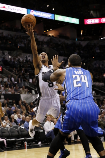Oct 22, 2013; San Antonio, TX, USA; San Antonio Spurs guard Patrick Mills (8) drives to the basket as Orlando Magic forward Romero Osby (24) defends during the second half at AT&T Center. The Spurs won 123-101. Mandatory Credit: Soobum Im-USA TODAY Sports