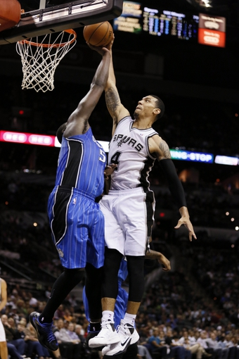 Oct 22, 2013; San Antonio, TX, USA; San Antonio Spurs guard Danny Green (4) goes up for a dunk while defended by Orlando Magic forward Jason Maxiell (54) during the second half at AT&T Center. The Spurs won 123-101. Mandatory Credit: Soobum Im-USA TODAY Sports